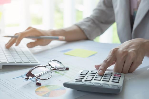 Chiuda su della penna di tenuta della mano del ragioniere o dell'uomo d'affari che lavora al calcolatore