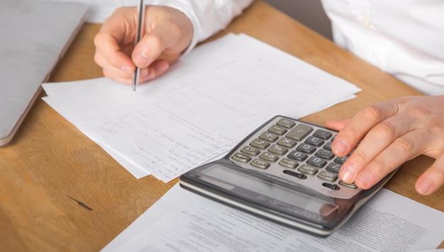 Chiuda su della penna di tenuta della mano del ragioniere o dell'uomo d'affari che lavora al documento di contabilità del calcolatore e al computer portatile all'ufficio, concetto di affari