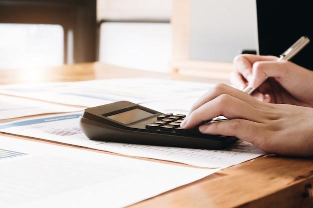 Chiuda su della penna di tenuta della mano del ragioniere o della donna di affari che lavora al calcolatore per calcolare i dati di gestione