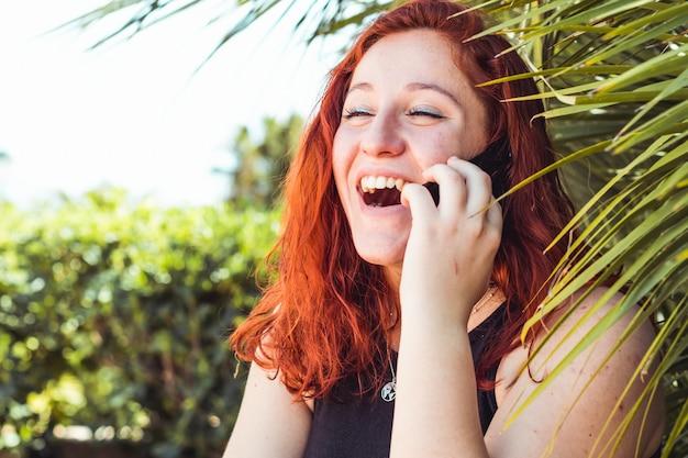 Chiuda su della ragazza attraente sorridente con la testarossa che parla sul telefono cellulare mentre stanno all'aperto