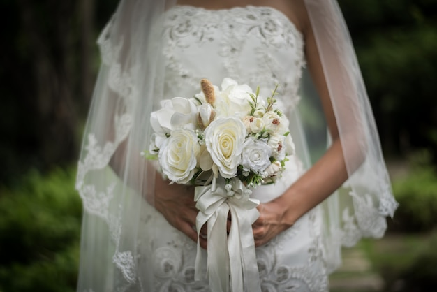 Chiuda su della sposa con il fiore nuziale di nozze in mani.