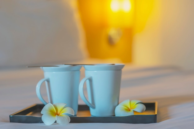 Chiuda su della tazza di caffè di benvenuto gemellata sul letto bianco nella camera di albergo - concetto di viaggio di vacanza di ospitalità dell'hotel bene