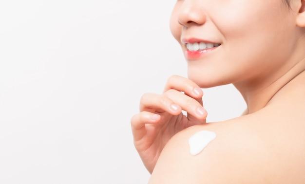 Chiuda su della tenuta asiatica sorridente della mano della donna e dell'applicazione della crema idratante sulla spalla, lozione del corpo, isolata sulla parete bianca
