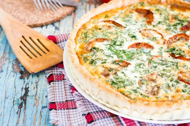 Chiuda su della torta casalinga della quiche francese con il pomodoro, il formaggio e l'erba su un piatto su una tavola di legno