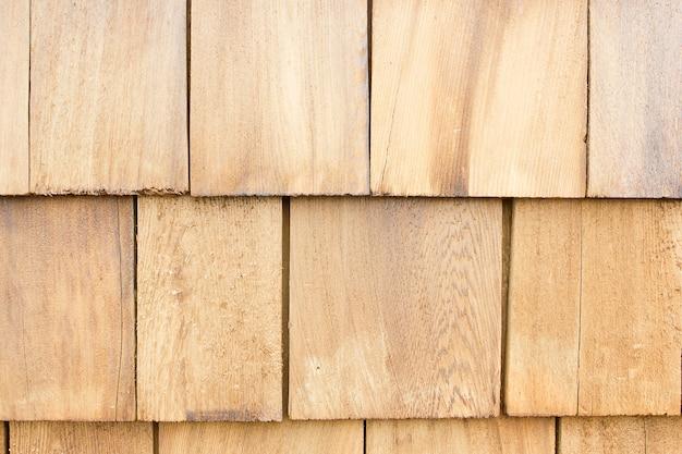 Chiuda su delle assicelle di legno marroni del tetto. fondo di legno.