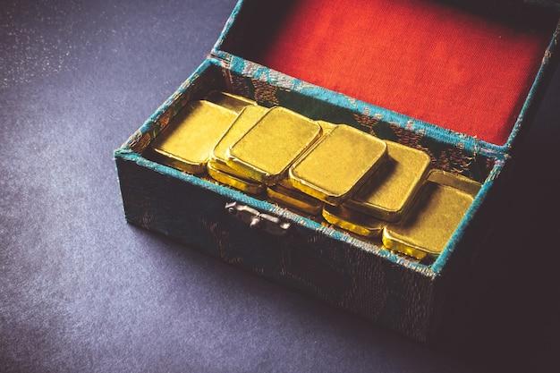 Chiuda su delle barre di oro pure nella scatola su fondo scuro.