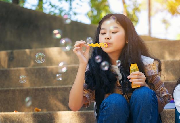 Chiuda su delle bolle di sapone di salto del bambino e si divertono nel parco dell'estate all'aperto