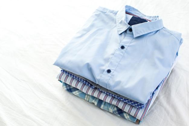 Chiuda su delle camice stirate e piegate sulla tavola a casa