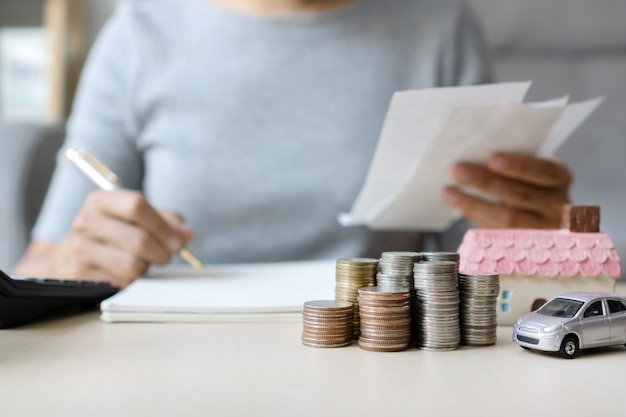 Chiuda su delle fatture della tenuta della mano mentre scrivono, pila di monete, casa del giocattolo ed automobile sulla tavola, risparmiando per il futuro, riescono al concetto di successo, di affari e di finanza.