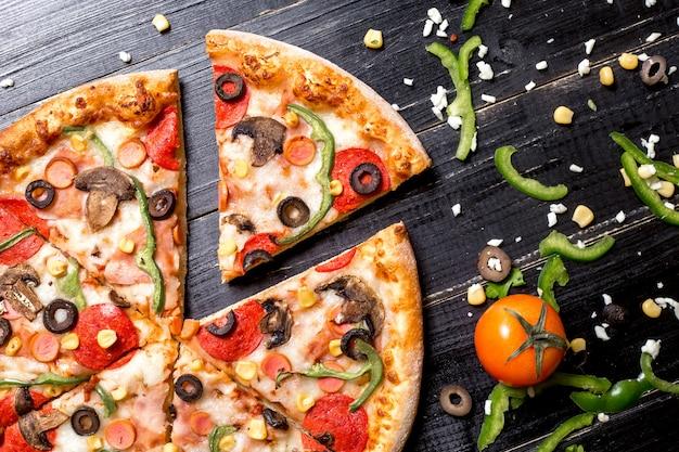 Chiuda su delle fette della pizza di merguez con il peperone dolce e il formaggio verde oliva del salame