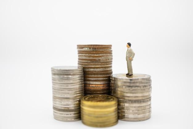 Chiuda su delle figure miniatura dell'uomo d'affari che stanno sulla pila di monete