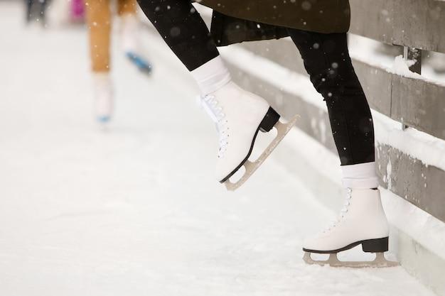 Chiuda su delle gambe del pattinatore della donna alla pista di pattinaggio aperta, vista laterale. pattini bianchi femminili su ghiaccio, treni vicino al muro, imparando a bilanciare. attività del fine settimana all'aperto quando fa freddo.