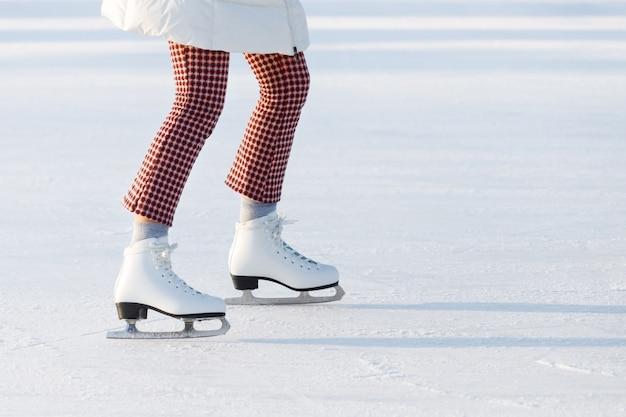 Chiuda su delle gambe della donna in pantaloni controllati rossi sui pattini su una pista di pattinaggio aperta, copi lo spazio. giorno soleggiato.