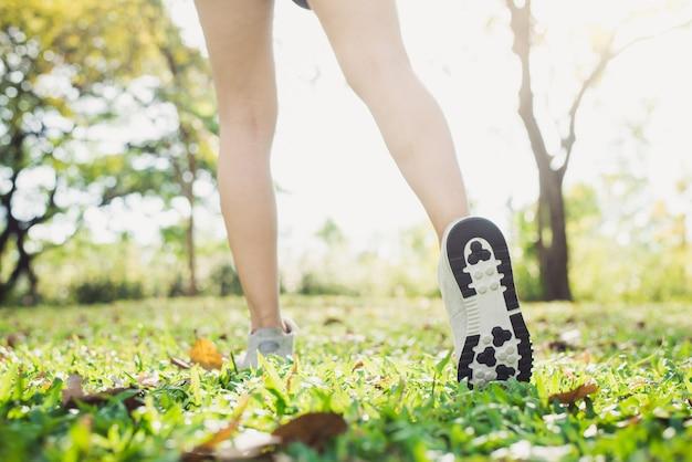 Chiuda su delle gambe di una giovane donna nel riscaldamento del corpo allungando