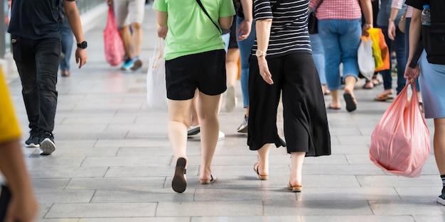 Chiuda su delle gambe e delle scarpe che camminano sulla via nella città