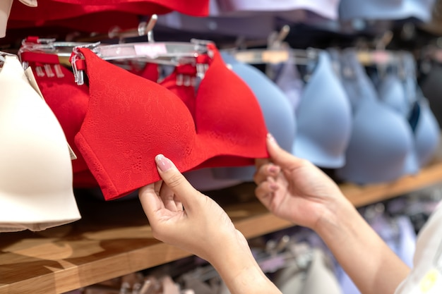 Chiuda su delle mani che scelgono le dimensioni delle tazze dei reggiseni.