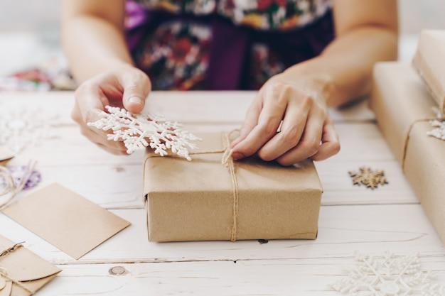 Chiuda su delle mani che tengono il contenitore di regalo di spostamento sulla tavola di legno con la decorazione di natale.