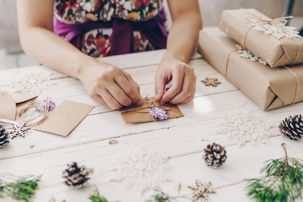Chiuda su delle mani che tengono il contenitore di regalo e la cartolina di natale di spostamento sulla tavola di legno con la decorazione di natale.