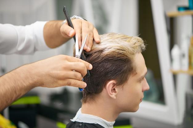 Chiuda su delle mani del barbiere che fanno il nuovo taglio di capelli per il giovane cliente.