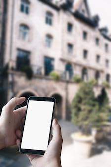 Chiuda su delle mani dell'uomo con il messaggio mandante un sms dello smartphone sul fondo vago via della città. schermo vuoto per il montaggio del display grafico.