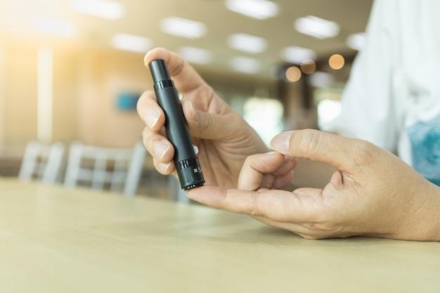 Chiuda su delle mani dell'uomo facendo uso della lancetta sul dito per controllare il livello della glicemia dal metro del glucosio. utilizzare come medicina, diabete, glicemia, assistenza sanitaria e concetto di persone.