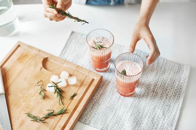 Chiuda su delle mani della donna che decorano il frullato sano della disintossicazione del pompelmo con rosmarino.