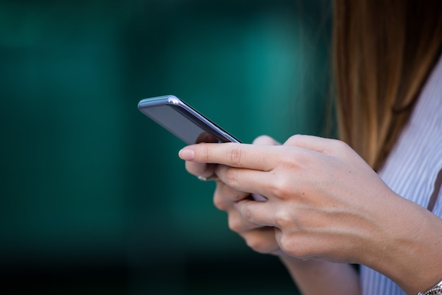 Chiuda su delle mani delle donne che tengono il telefono delle cellule con lo schermo in bianco per il messaggio di testo o il contenuto promozionale