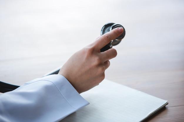 Chiuda su delle mani di medici con lo stetoscopio, gli strati e le pillole su fondo di legno