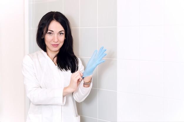 Chiuda su delle mani di medico femminile che indossano i guanti chirurgici sterilizzati blu nella clinica medica