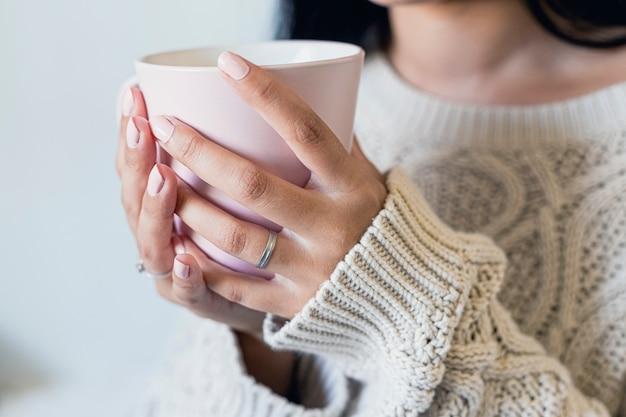 Chiuda su delle mani di una bella giovane donna che tengono una tazza di caffè caldo in attrezzatura dell'inverno a casa