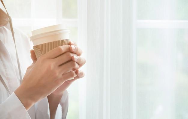 Chiuda su delle mani di una donna che tengono una tazza di caffè calda vicino alla finestra a casa
