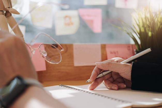 Chiuda su delle mani femminili che scrivono in blocco note a spirale disposto e tengono i vetri sul desktop di legno.