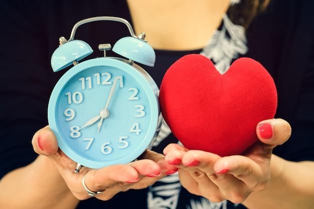 Chiuda su delle mani femminili che tengono la sveglia e la forma del cuore
