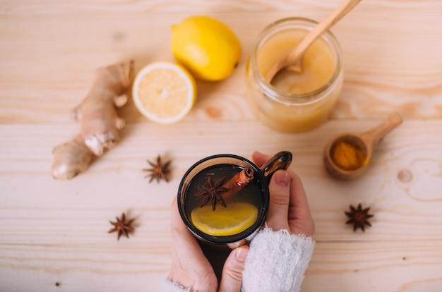 Chiuda su delle mani femminili che tengono la tazza di acqua calda con il limone