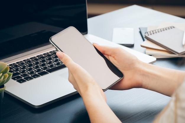 Chiuda su delle mani femminili facendo uso dello smartphone alla tavola dell'ufficio