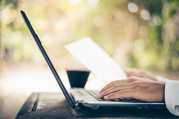 Chiuda su delle mani maschii che scrivono sulla natura del fondo della tastiera del computer portatile