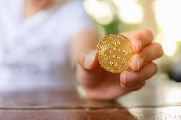 Chiuda su delle monete del bitcoin dell'oro della tenuta della mano dell'uomo sulla tavola di legno.