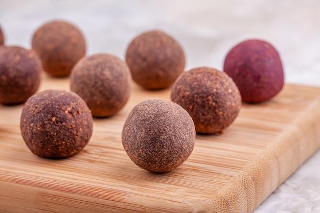 Chiuda su delle palle crude casalinghe di energia del cacao del vegano sul vassoio di legno sulla tavola