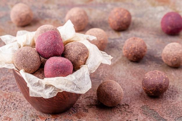 Chiuda su delle palle di energia crude casalinghe del cacao del vegano in ciotola con la carta del mestiere