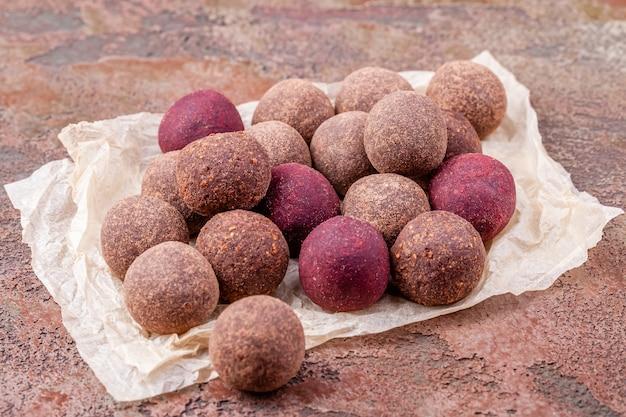 Chiuda su delle palle di energia crude casalinghe del cacao sulla carta del mestiere