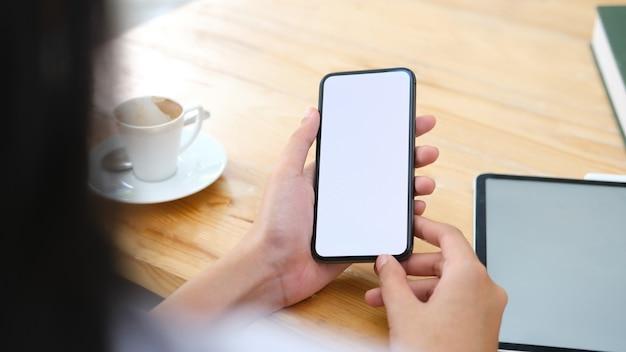 Chiuda su dello smart phone della tenuta della mano dell'uomo.