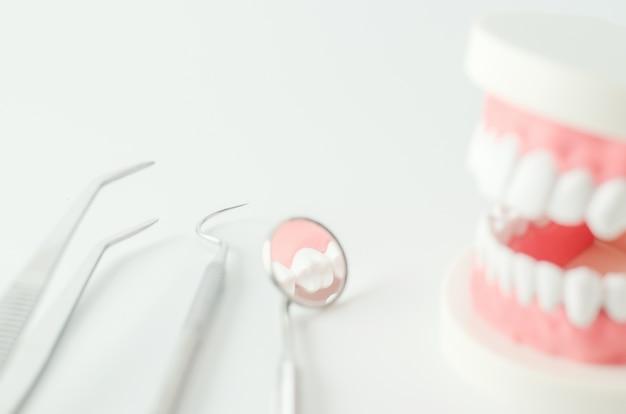 Chiuda su dello specchio dentario con i denti modellano e l'attrezzatura dentaria su fondo bianco