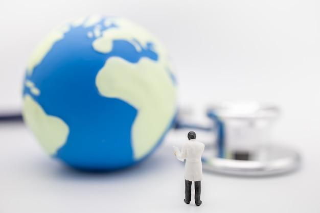 Chiuda su dello stanind miniatura della figura del medico con il diagramma paziente con la mini palla del mondo e stetoscopio.
