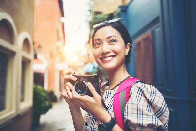 Chiuda su dello zaino della donna dei giovani pantaloni a vita bassa che intraprende la presa della foto con la sua macchina fotografica in urbano.