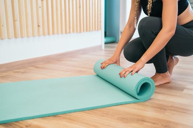 Chiuda su di bella giovane donna che piega la stuoia di yoga del turchese dopo avere risolto a casa