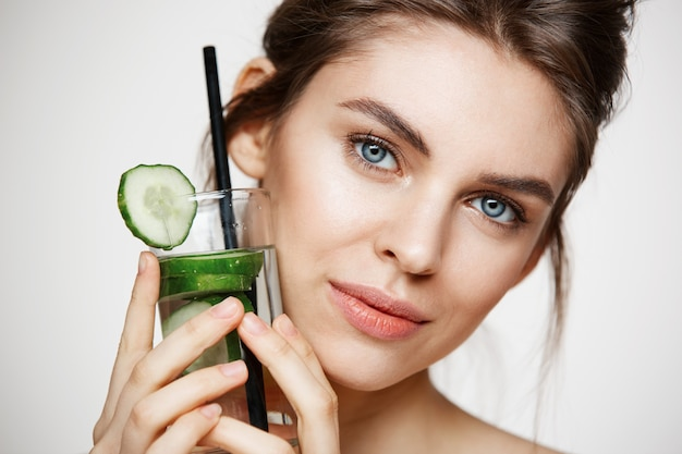 Chiuda su di bella ragazza nuda che sorride esaminando la macchina fotografica che tiene il bicchiere d'acqua con le fette del cetriolo sopra fondo bianco. nutrizione sana. bellezza e cura della pelle.