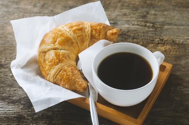 Chiuda su di caffè nero con il croissant sulla tavola di legno con il tono di scenetta e dell'annata