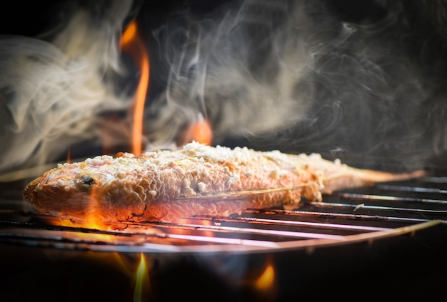 Chiuda su di cibo per pesci grigliato frutti di mare con sale sul fuoco e sul fumo della griglia
