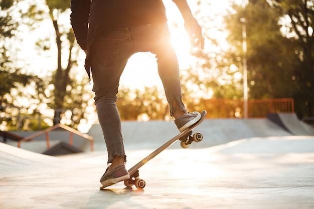 Chiuda su di giovane addestramento maschio dello skateboarder nel parco del pattino