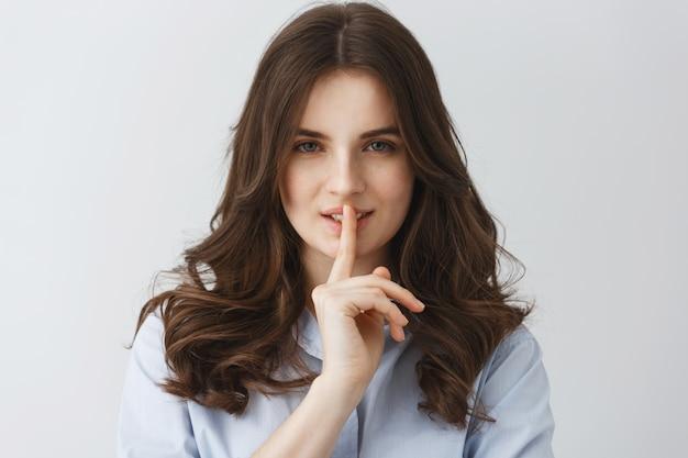 Chiuda su di giovane dito sexy della tenuta della ragazza vicino alla bocca che fa il gesto di silenzio con l'espressione civettuola del fronte.